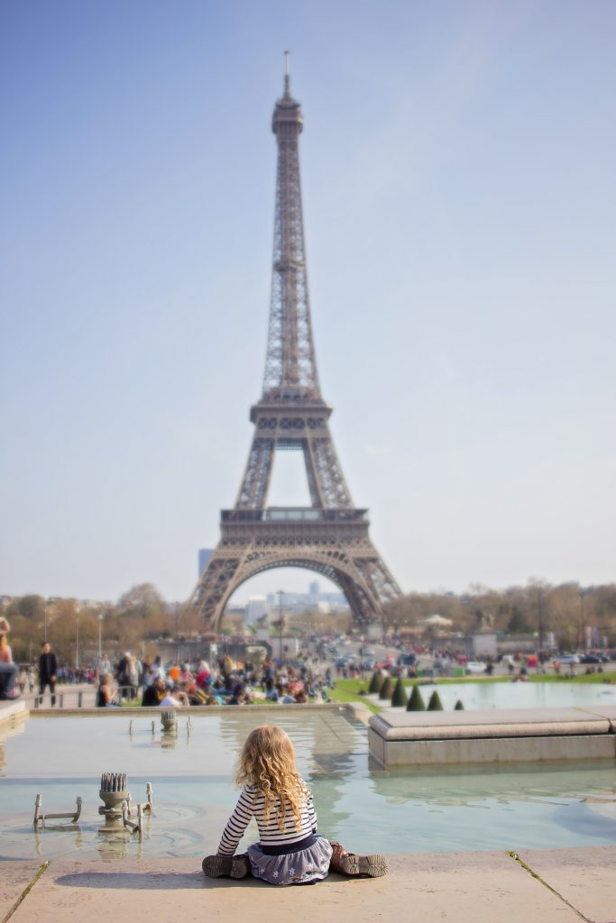 Girl sits in front of Eiffel Tower in Paris