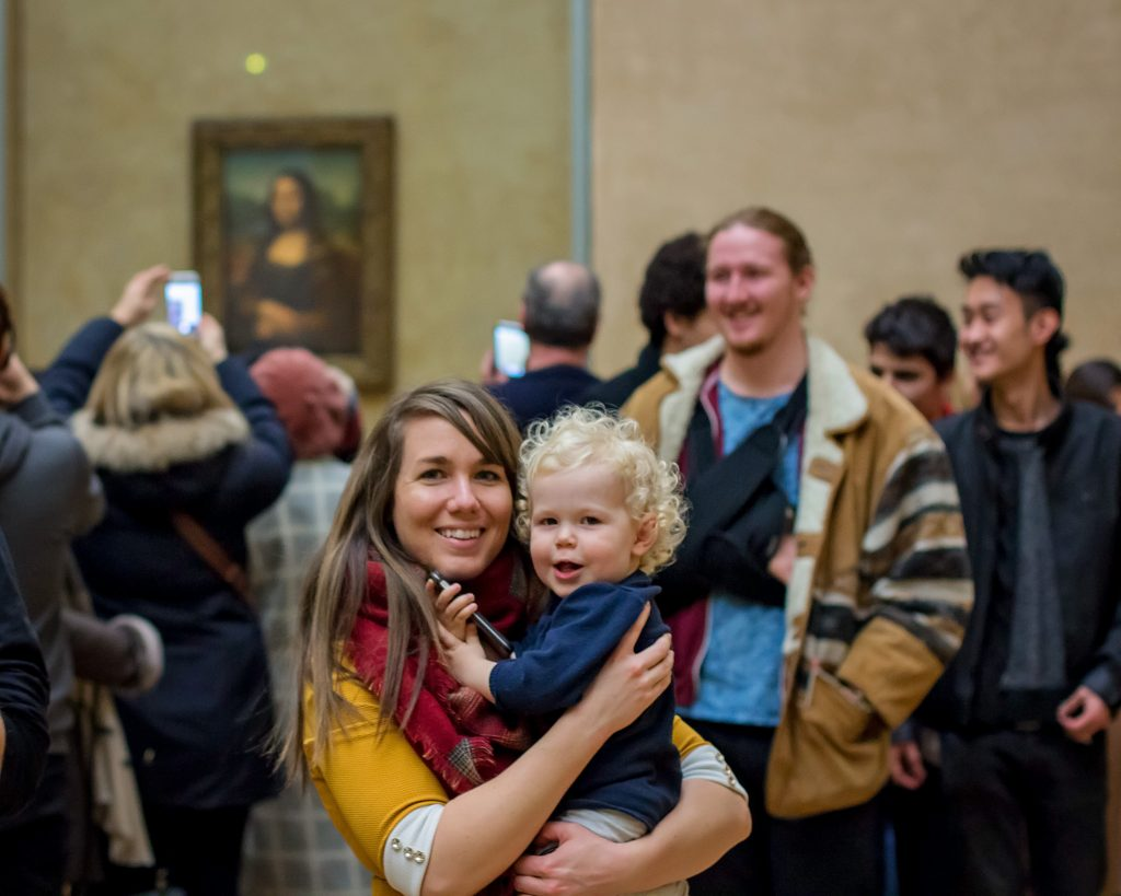 Mother and son view Mona Lisa in the Louvre