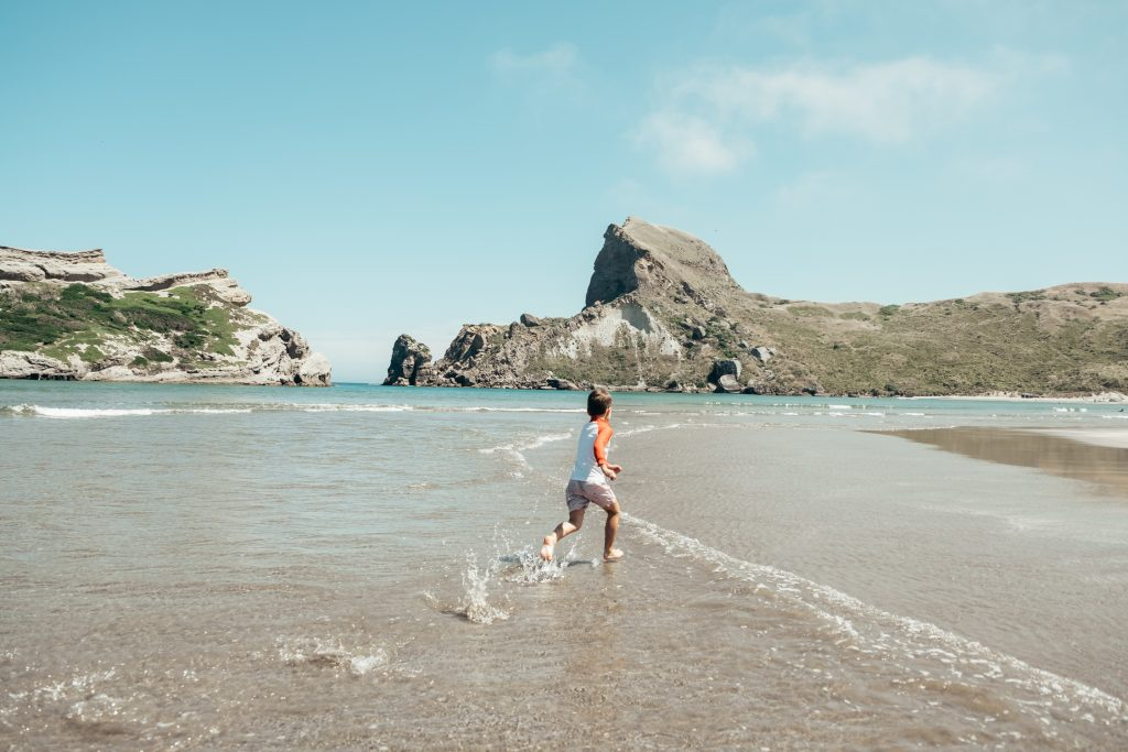 Boy running on Castlepoint Beach in New Zealand