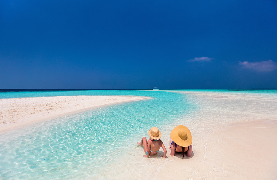 Family relaxing on beach in Maldives