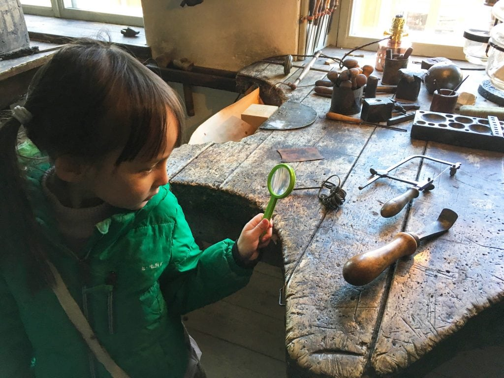 Things to do in Stockholm with kids_Girl in Skansen looking at blacksmith tools