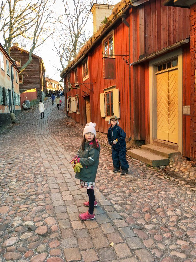 Things to do in Stockholm with kids: Girl walking through Skansen village